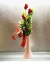 Three red roses with green foliage in a beige vase with a red satin ribbon